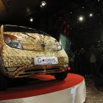 Photographers take pictures of a Tata Nano car made of gold during a ceremony in Mumbai