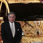 Chairman of Tata Group Ratan Tata poses in front of a Nano car made of gold during a ceremony in Mumbai