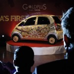 People watch the unveiling of a Tata Nano car made of gold during a ceremony in Mumbai