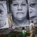 People walk past large portraits of women whose children were victims of violence, in Caracas