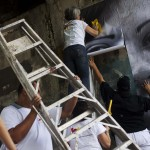 Volunteers put up a large portrait of a woman whose son was a victim of violence, in Caracas