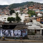 Volunteers put up large portraits of women whose children were victims of violence, in Caracas