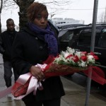 Woman carries bouquet of roses to makeshift memorial outside The New Hope Baptist Church in Newark site of the funeral for Whitney Houston