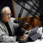 Reporter Bocaranda looks at a tablet computer during his radio program in Caracas