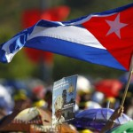 A person waves a Cuban flag while a sign showing Pope Benedict XVI is seen in the foreground, as people wait at Revolution Square in Havana