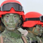 A group of Taiwanese women paratroops pose for photos after a drill held at Taiwan's northern Hsinchu airbase on April 19, 2012.  Taiwan tested its ability to defend one of its largest air bases against Chinese invasion, a scenario experts insisted remained relevant in an age of missile and cyber attacks.    AFP PHOTO / Mandy CHENG