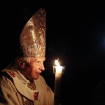 Pope Benedict XVI prays while holding a candle light as he arrives to lead a vigil mass during Easter celebrations in the Vatican