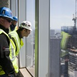 Construction workers look out the windows of the 71st floor of One World Trade Center in New York