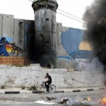 A Palestinian rides his bike past the controversial Israeli separation barrier and burning tires close to the Aida Palestinian refugee camp, near the Biblical city of Bethlehem, in the Israeli occupied West Bank, on May 14, 2012, as Palestinians mark the 64 anniversary  of the Nakba or