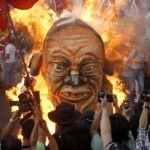 Protesters burn an effigy of President Aquino as thousands of workers rally in Manila