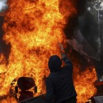 A demonstrator throws glass into a fire during May Day rallies in Santiago
