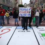 A protestor stands on a mock Monopoly game board on the street during May Day demonstrations in Los Angeles