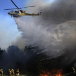 A Los Angeles county helicopter makes a water drop to help firefighters battle a brush fire in Acton, California