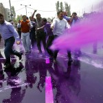 Government employees are hit by dyed water from a cannon used by Indian police to disperse a protest by the employees in Srinagar