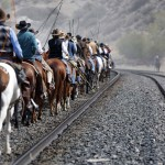 Wranglers travel up a train rail line during Montana Horses' annual horse drive outside Three Forks