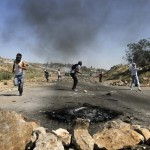 Palestinians throw stones during clashes with Israeli security forces, near Ramallah