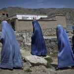 Afghan women clad in burqa walk up a hill at the old part of Kabul