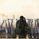 A Somali government soldier, dressed in Uganda People's Defence Forces uniform and trained by the European Union Training Mission team, sits with rifles during passing out ceremony at Bihanga army training school