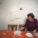 Francisca Garcia sets the table at the living room of her house that was damaged by Lorca's earthquake one year ago, in Lorca