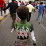Youth, with his back painted with the colours of Syria's opposition flag, marches during a demonstration demanding that relatives of former president Ali Abdullah Saleh be dismissed from senior army and police posts in Sanaa