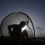 A man is silhouetted against the sun as he sits in a mosquito net early morning atop of a tanker in Karachi