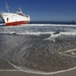 A tugboat attempts to refloat fishing vessel Eihatsu Maru which ran aground at Clifton