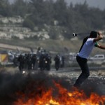 A Palestinian protester uses a sling to hurl stones at Israeli troops during clashes outside Ofer prison near Ramallah