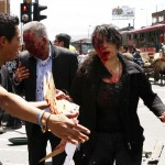Injured people, with blood on their faces, walk after an explosion in a central avenue in Bogota