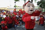 A person wearing a costume and a mask resembling Venezuela's President Hugo Chavez, dances on stage an United Socialist Party campaign rally, in Caracas