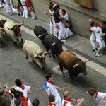 Runners sprint in front of Cebada Gago ranch fighting bulls on Santo Domingo street during the third Running Of The Bulls in Pamplona