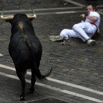 A runner falls in front of Fugado a 545 kg Cebada Gago fighting bull, on Santo Domingo street during the third Encierro Running Of The Bulls in Pamplona
