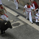 Runners sprint alongside a Cebada Gago ranch fighting bull on Santo Domingo street during third Running Of The Bulls at San Fermin festival in Pamplona