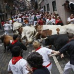 Runners sprint alongside Cebada Gago ranch fighting bulls on Santo Domingo street during the third Running Of The Bulls at the San Fermin festival in Pamplona