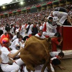 A wild cow leaps over a group of revellers following the third day of the running of the bulls at the bullring during the San Fermin festival in Pamplona