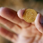 Israel Nature and Parks Authority employee holds up a gold coin, which was unearthed during excavations at a Crusader fortress near Herzliya