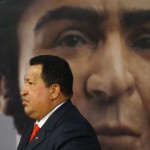Venezuelan President Chavez walks past an image of independence hero Bolivar during a ceremony in Caracas