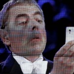 Actor Rowan Atkinson is seen on a giant screen as he performs during the opening ceremony of the London 2012 Olympic Games at the Olympic Stadium