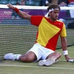 Spain's Ferrer falls as he and Lopez face France's Llodra and Tsonga in their men's doubles tennis semi-final match at the All England Lawn Tennis Club during the London 2012 Olympic Games