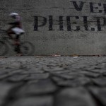 A man rides his bike past graffiti that reads