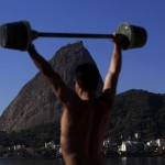 Men work out using improvised weights with Sugar Loaf Mountain in the background in Rio de Janeiro