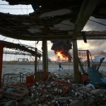 Fire is seen in the affected area after an explosion at Amuay oil refinery among debris the of a building in Punto Fijo in the Peninsula of Paraguana