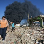 People walks among debris in the area close to the explosion at Amuay oil refinery in Punto Fijo in the Peninsula of Paraguana