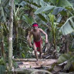 A Yanomami Indian runs in the jungle at the community of Irotatheri
