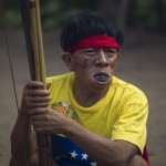 A Yanomami Indian watches a dance as he chews leaves at the community of Irotatheri