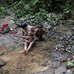A Yanomami Indian baths a child at a river at the community of Irotatheri