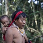 A Yanomami Indian walks as she carries a baby at the community of Irotatheri
