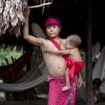 A Yanomami Indian woman stands at her shack at the community of Irotatheri