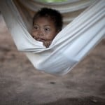 A Yanomami Indian boy looks on at a hammock at the community of Irotatheri