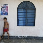 Children stand at a door of their house, which is located in Venezuela President Hugo Chavez's chilhood town of Los Rastrojos, in the state of Barinas