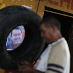 A man works in his mechanical garage in Barinas next to a campaign poster of Venezuelan President Hugo Chavez